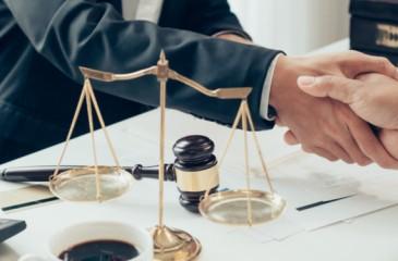Ein Anwalt schüttelt seinem Mandanten die Hand