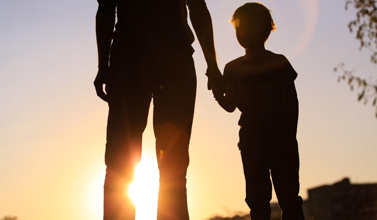 Vater hält die Hand eines Kindes im Sonnenuntergang