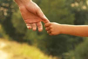 Vater hält Hand seines Kindes