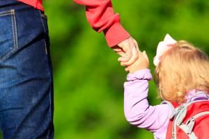 Ein Kind hält die Hand eines Mannes