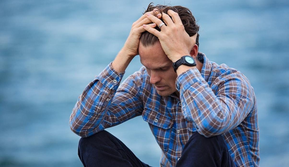 Trauriger Mann sitzt am Wasser