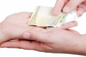 Eine Hand gibt einer anderen Geld