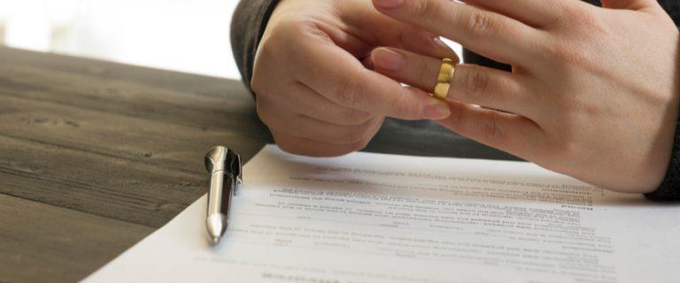 Ehemann unterschreibt Scheidungspapiere und nimmt seinen Ring ab