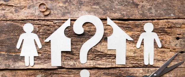 Zerschnittene Papierfiguren einer Frau, eines Mannes und eines Hauses mit einem Fragezeichen in der Mitte