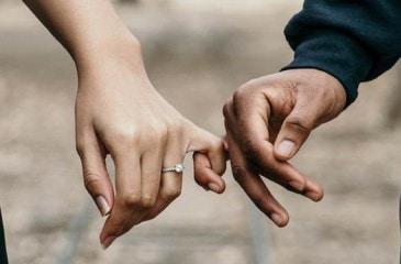 Frisch verheiratetes Ehepaar hält sich mit dem kleinen Finger fest.