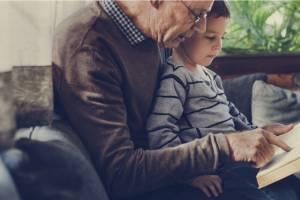 Opa liest seinem Enkel etwas vor