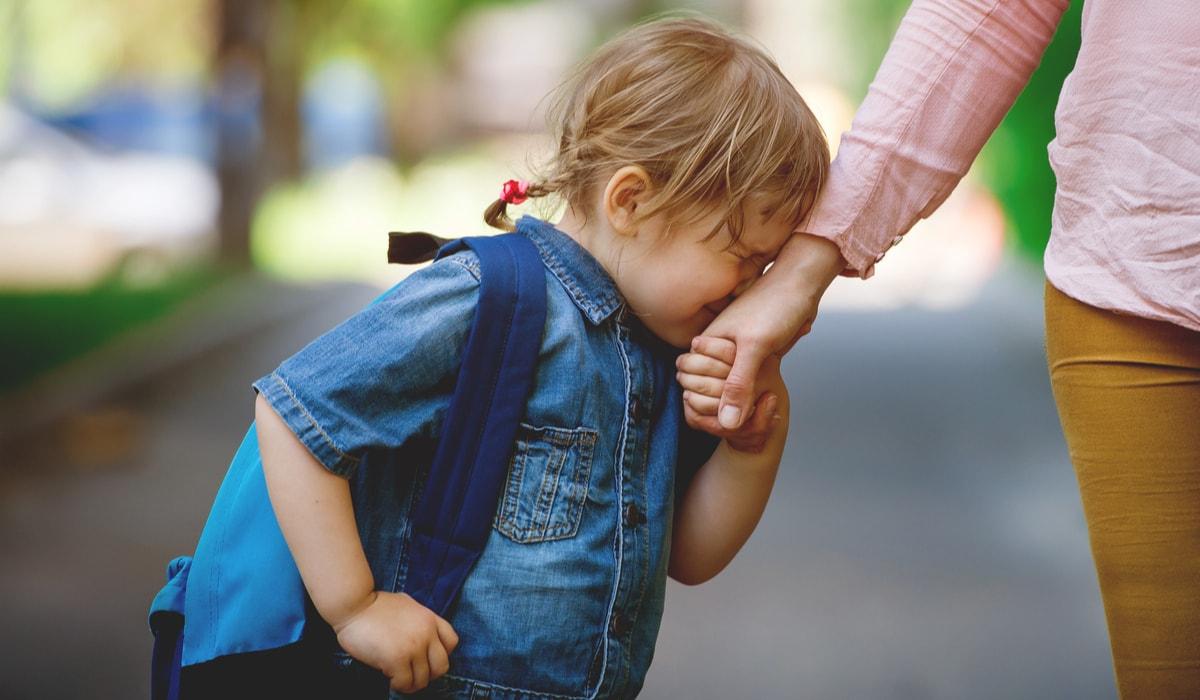 Kind weint und klammert sich an die Hand der Mutter