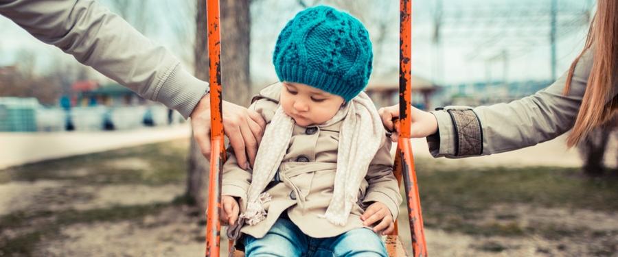 Eltern streiten sich um ein Kleinkind, das auf einer Schaukel sitzt