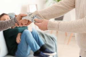 Mann und Frau streiten sich um Geld, während das Kind auf einer Couch sitzt