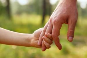 Vater hält Hand eines Kindes